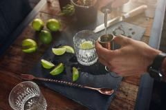 Pouring alcohol in jigger to prepare a cocktail - stock photo