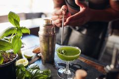 Bartender preparing fresh basil smash cocktail Stock Photos