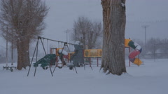 Snow falling on childrens empty play ground Stock Footage