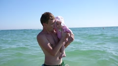 Father hold swim with suckling baby daughter at sea water family summer weekend Stock Footage