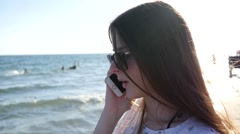 Pretty teenager girl long hair stay by sea talk over smart phone summer resort Stock Footage