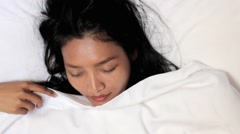 Portrait of a young woman sleeping on a white pillow under the duvet Stock Footage