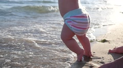 Little baby child legs and toes touch sand on sea beach walking into small waves Stock Footage