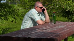 Man talking on the phone near bottle of alcohol on table - stock footage