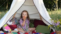 Little child girl playfully sit and eat an apple in a tent during picnic Stock Footage