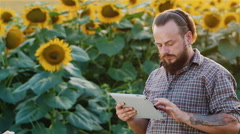 Attractive bearded farmer working with the tablet. Against the backdrop of a Stock Footage