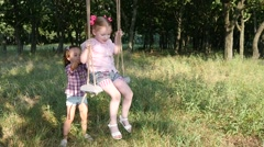 Sway on swing two little girls play in a nature forest park Stock Footage