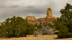 Desert wind blows juniper trees stone tower in background Stock Footage