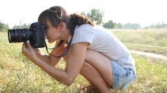 Young woman photographer at working process shooting outdoors in nature Stock Footage