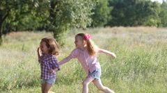 Two cute little kid girls run chase catch each other have fun in nature park  Stock Footage