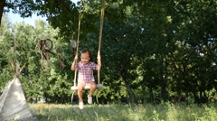Little child girl have fun swaying on swing slow motion in nature forest park Stock Footage