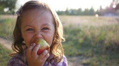 Cute little kid girl portrait stay eat chew an apple on nature sunset picnic Stock Footage