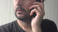 Handheld shot of casual male talking on mobile phone - stock footage
