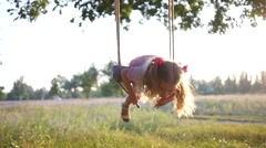Little cute blonde child girl funny sway lying on swing on nature sunset light Stock Footage