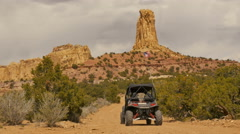 Side by side off road vehicle drives away desert road toward rock to Stock Footage
