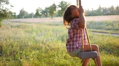 Happy cute little child girl have fun sway spin on a swing on nature sunset Stock Footage