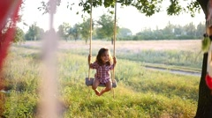 Happy little child girl have fun play sway on swing on nature sunset time - stock footage