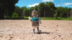 Robot Toy walking down the street Stock Footage