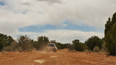 White SUV driving away on dusty desert road Stock Footage