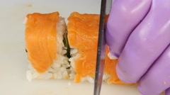 Sushi chef prepares the rolls cut pieces. Close up Stock Footage