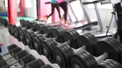 Dumbbells layout stand in a gym and people training on background Stock Footage