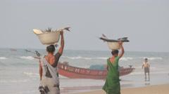 Women carrying big fish in basket on head,Puri,India Stock Footage