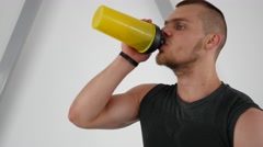 Young guy bodybuilder drink protein cocktail during hard training muscles in gym Stock Footage