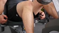 Sport man legs spinning peddals of exercise bike in a gym Stock Footage