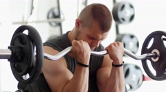 Sports bodybuilder young man hard training biceps muscles in gym Stock Footage
