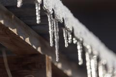 Long and dangerous icicles on a house roof - stock photo
