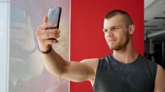 Young strong guy in gym doing selfie photo for social media instagram Stock Footage