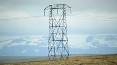 Electrical pylon environmental impact snow covered mountain glacier Iceland Stock Footage