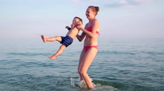 Cheerful mother with a baby circles around in the water smiling and waving Stock Footage