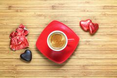 Heart shaped sweets wrapped in a bright red foil lying on wooden texture with Stock Photos