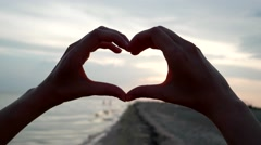 Heart Hands show at sunset on the beach, the sun looks into the camera Stock Footage