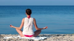 Meditation, the practice of yoga on the sandy beach, a beautiful slim girl on Stock Footage