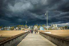Dark storm clouds over the fishing pier and beach in Venice Beach, Los Angele Stock Photos