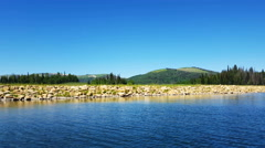 Gliding past rocky shore clear blue mountain lake Stock Footage