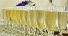 Elegant glasses with champagne standing in a row on serving table during party Stock Footage