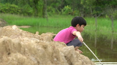 Young asian boy playing in mud puddle near the river Stock Footage