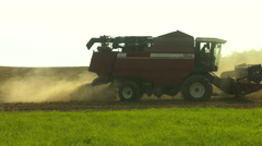 Generic combine harvester harvesting wheat with dust straw in the air Stock Footage