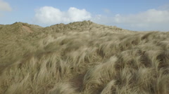 Aerial shot moving across sand dunes & out to Sea Stock Footage