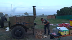 Field Kitchen. Evening Time. Man Taking Care of the Fire Stock Footage