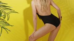 Beautiful young woman posing in black swimsuit over yellow background. - stock footage