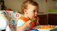 Baby is eating spaghetti with a fork - stock footage