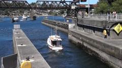 Motorboat leaves the Hiram Chittenden Locks Stock Footage
