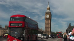 London red bus as it passes big ben and tourists walk along bridge - stock footage