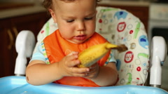 Sweet baby is looking on a banana at the kitchen Stock Footage
