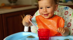 Happy baby is drinking and playing at the kitchen Stock Footage
