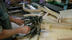 Woodwork taking clamps off bent wood Stock Footage